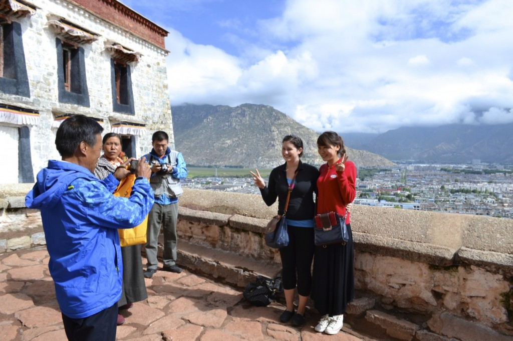 Taking photos with a pilgrim family at the Potala Palace